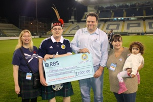 Graeme Baxter and Dot Wilson present the cheque to Panayiotis Savvides from the Cyprus Autistic Association prior to the match in Larnaca