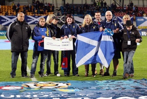 June Callison with Dot Wilson, Graeme Shinnie and John Daly present a cheque to families from Unanders immediately prior to the match in Vaduz
